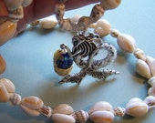 MERMAID has tiny basket of genuine ENGLISH SEAGLASS pieces. Long shell necklace.Silvertone Mermaid with clear glass glitter on tail.  21.00