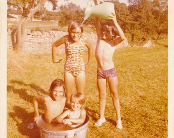 "1970s Snapshot Photo - ""Cooling Off"" - Children Sitting In Tin Bath - Boy Pouring Jug Of Water Over Girl"