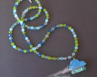 """Car necklace made with """"It's a Mad, Mad, Mad, Mad World"""" shatter glass."""