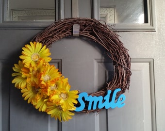 14 inch grapevine wreath with yellow flowers and blue wording