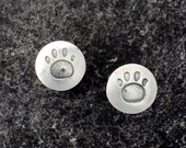 Paw-print stud earrings in sterling silver.