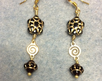 Black Czech glass turtle bead dangle earrings adorned with gold swirly connectors and black Saturn beads.