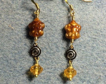 Yellow gold marbled Czech glass turtle bead dangle earrings adorned with gold swirly connectors and yellow Saturn beads.
