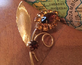 Beautiful vintage gold tone flower pin with brown and gold colored rhinestones