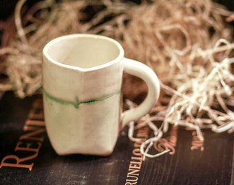 Hand-built mug with with creamy white glazes with green accents