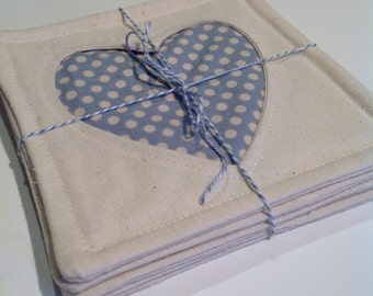 Fabric coasters with heart inlay using inverse applique, contrasting patterns, in duck-egg blue