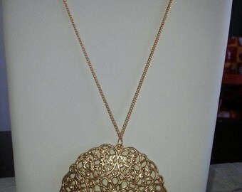 A long goldfiled necklace with a large Medallion. 5 cm pendant and Chain length 74 cm