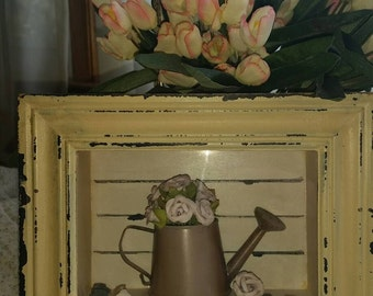 Shadow box with watering can and flowers.
