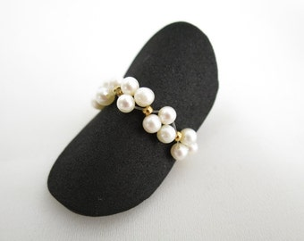 Elastic ring with white cultured pearls and goldplated beads, one size, fits to all fingers.