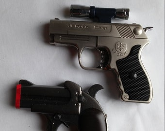 2 Butane Lighters Mfg. In China.  Both look like guns.  Both in working condition. One has a laser like sighting.