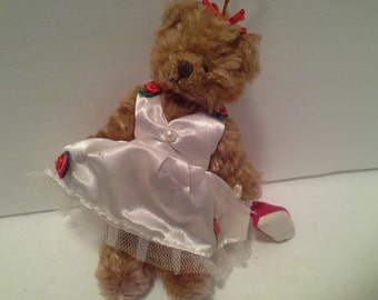 Little bear in party dress with red slippers