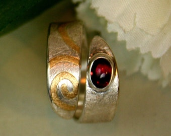 Open ring with Garnet and spiral motif