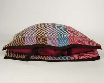 Handwoven cushion of linen. Weaving many-coloured mauve, brown, blue and raspberry. One of a kind and original weaving.