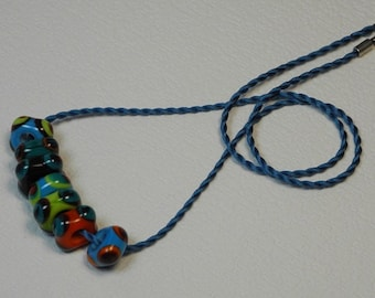 Necklace, ras neck cord of silk Mokuba, with 7 glass square, ornate points, turquoise, orange, green and Garnet beads.