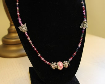 Pink beaded necklace with butterflies