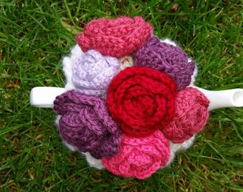 White hand knitted tea cosy with red/ purple hand crocheted flowers, tea pot is not included.