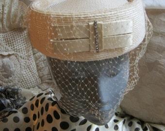 Vintage retro cream beige pillbox with netting, bride's pearl beige shaped veiled hat, ribbon rhinestone bow detail woven pillbox hat