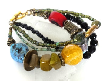 Multi strand bracelet of onyx, turquoise, brass and large statement beads in deep primary colors