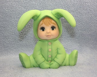 Handpainted Ceramic Adorable Baby sitting while wearing a  lime green bunny outfit
