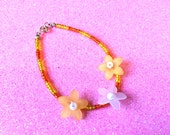 Orange and Yellow glass rocaille seed bead bracelet with orange and white plastic summer flowers