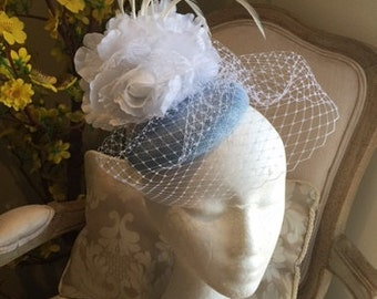 Lovely light blue fascinator with 2 lace white flowers, feathers & netting!