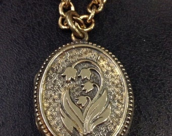 Vintage locket , oval with flowers gold tone