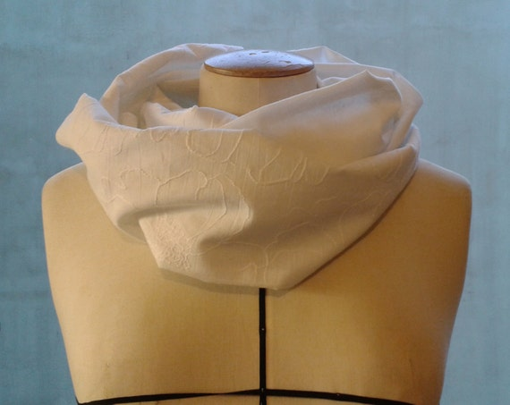 "SNOOD: scarf veil of white cotton, embroidered flowers on one side. Sewn in ""tube"", two laps."