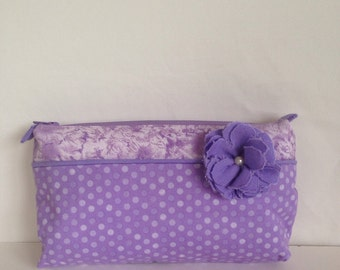 Purple two-toned cosmetic bag, make-up bag, zippered pouch, storage bag with a flower accent.