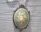 Fairy Cameo - light  blue background w/ off white raised relief fairy, on 925 Sterling Silver, antiqued silver bezel, 40mm by 30mm, OOAK