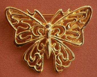 B429)  An elegant gold tone metal filigree butterfly brooch