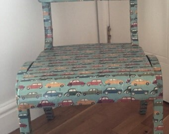A child's chair decopatched/decoupaged in a car design