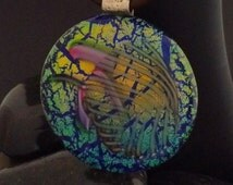 Blue, Green and Gold Dichroic Glass Pendant with Handmade Furnace Glass on a crackled background.
