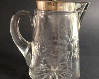 An Antique Heisey Cut Glass Syrup Pitcher with Silver Lid