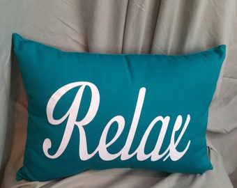 Teal pillow with White RELAX word printed on front.