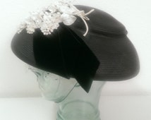 Black straw fascinator hat with white flowers and velvet ribbon on top