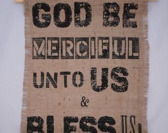 Scripture,  Bible Verse, 'God be merciful unto us and bless us'.  Psalm 67 v 1. KJV, AV version. Black text on stiffened Hessian Fabric.