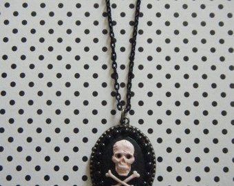 Peach skull and crossbones on black hand embellished with cabochons bronze oval pendant necklace