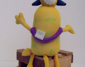 Sock Monster Made From Yellow Sock with Green Markings and One Eye with Blue Spikes and Four Legs and Purple Smile with One Sparkly Tooth