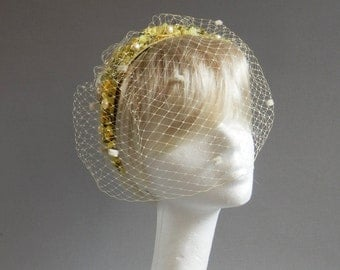 Dutch design yellow bridal headband embroided with lots and lots of beads and flowers and a birdcage veil.