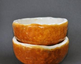 Set of two pinched orange bowls