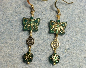 Emerald green Czech glass butterfly bead dangle earrings adorned with gold swirly connectors and emerald green Czech glass daisy beads.