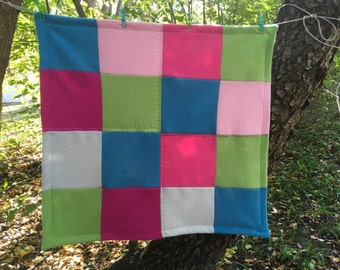 Upcycled, felted cashmere baby blanket in vibrant blues, greens and pinks with a sweet birdie motif flannel back