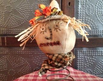 Primitive scarecrow head on a rusty spring