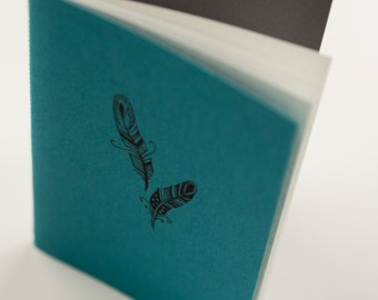 Turquoise blue hand made pocket-size notebook with couple grey sheets and feather drawing on cover