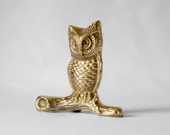 Large brass owl with red eyes sitting on a branch