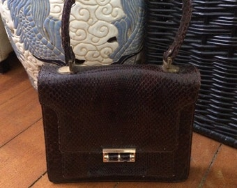 Heavy vintage leather top handle handbag in snake skin with vintage hand mirror.