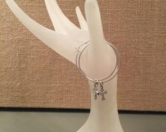 Sterling silver hoop earrings with a cross dangle