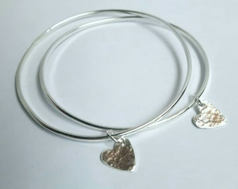 Silver bangle with a hammered heart charm.