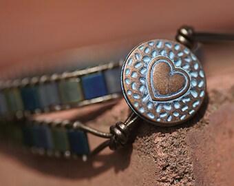 Handmade Miyuki Tila Patina double wrap bracelet with heart pattern button fastening.