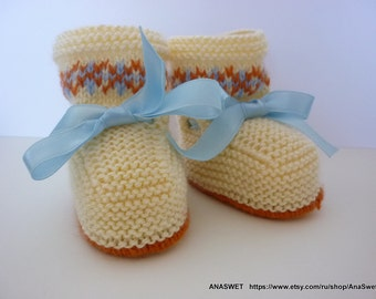 Knitted baby booties/slippers/shoes in natural colors with a blue ribbon